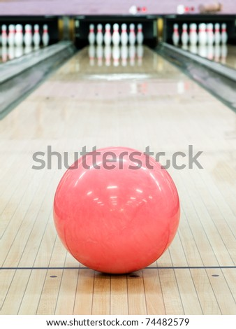 Pink sphere ball standing on bowling lane before strike - stock photo