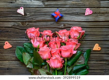 Pink stemmed rose bundle and various colored heart shapes with bowed gift boxes at center of full frame old wooden background with copy space