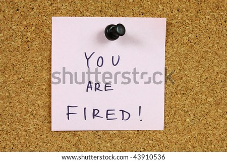 Pink sticky note pinned to an office notice board. You are fired - financial crisis, unemployment, career information.