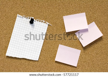 Pink sticky notes and pinned teared paper on brown corkboard - stock photo