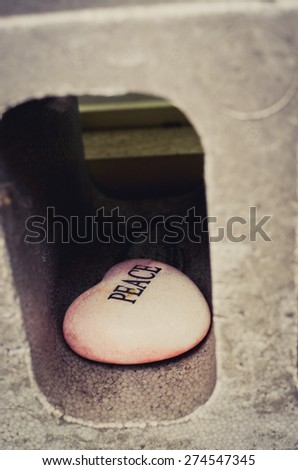 "Pink stone in shape of heart with word ""Peace"" on it.  The word ""Peace"" written on stone.  - stock photo"