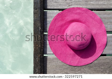 Pink straw hat on a wooden platform near the ocean. - stock photo