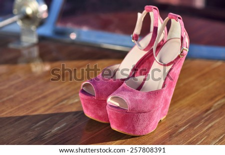 pink suede shoes isolated on wood yatch floor under summer sun - stock photo