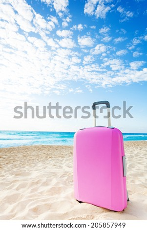 Pink suitcase baggage on the sand on the beach with blue sky - stock photo