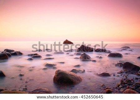Pink sunset at rocky coast of sea. Slow shutter speed for smooth water level and dreamy effect - stock photo