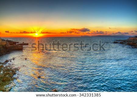 pink sunset over Alghero shoreline, Italy - stock photo