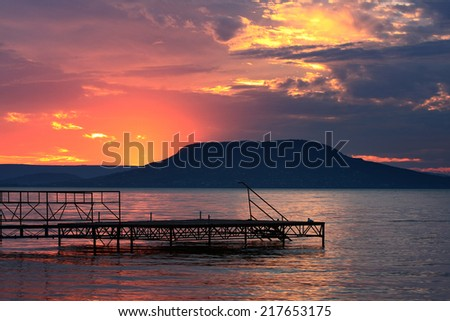 pink sunset over lake and hills - stock photo