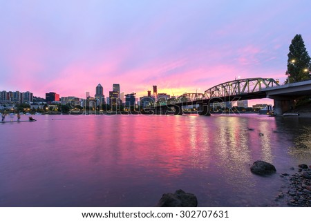 Pink Sunset over Portland Oregon downtown waterfront city skyline along Willamette River by Hawthorne Bridge - stock photo