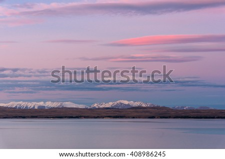 Pink sunset over Southern Alps and Lake Tekapo, Canterbury, South Island, New Zealand. Winter mountain landscape with lake on dusk with colorful pink sky  - stock photo