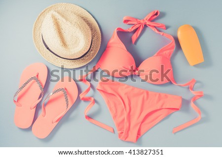 Pink swimsuit with beach accessories on blue background - stock photo