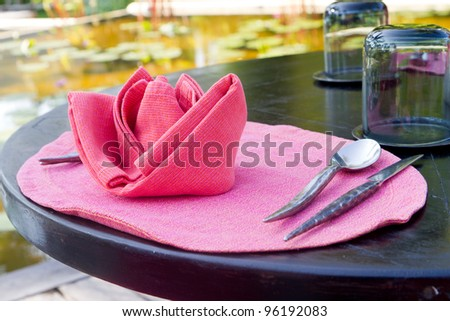 pink tablecloth with spoon and fork - stock photo
