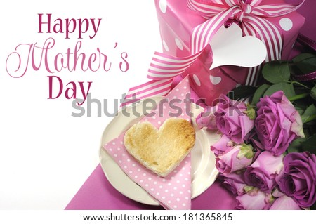 Pink theme breakfast with heart shaped toast, roses and polka dot gift with Happy Mothers Day sample text or copy space for your text here. - stock photo