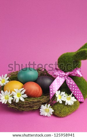 Pink theme Happy Easter scene still life with grass bunny rabbit with rainbow color eggs in a nest with white daisies. Vertical with copy space, your text here. - stock photo