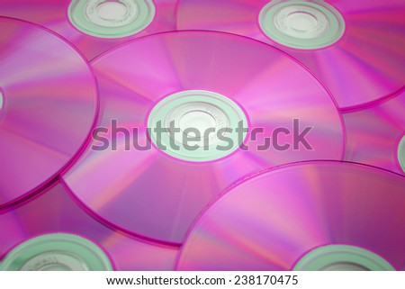pink tinted close-up of a stack of cd-roms - stock photo