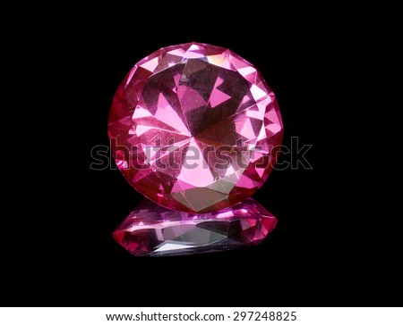 Pink topaz gemstone with reflection isolated on black background