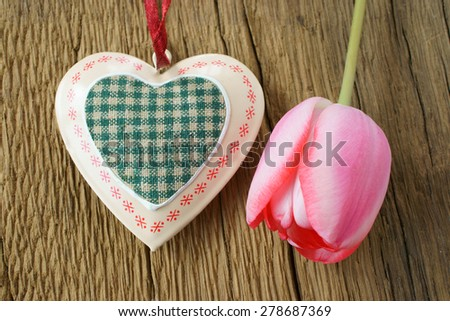Pink tulip and a heart on rustic wooden board - stock photo