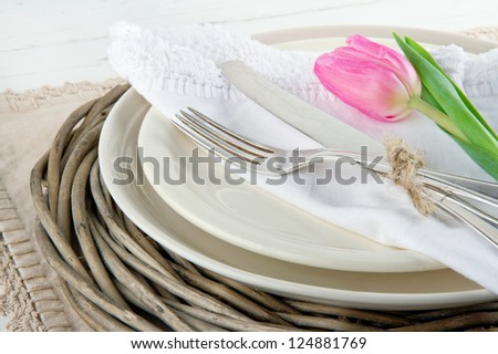 Pink tulip on rustic dinner setting on white wooden table