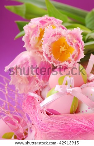 pink tulips  and colored eggs in pink basket as easter decoration