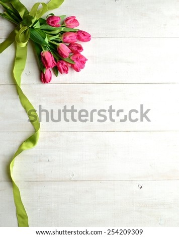 Pink tulips bouquet with yellow green ribbon. - stock photo
