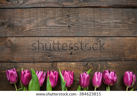 Pink, tulips bunch on dark barn wood planks background. Space for text, copy, lettering. Postcard template. - stock photo