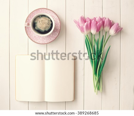 Pink tulips, coffee cup and notebook over white wood table ina flat lay composition