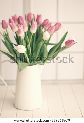 Pink tulips in a french cottage base over a white wood table  - stock photo