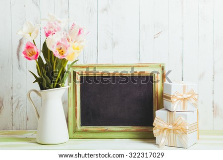 Pink tulips in jug and green wooden chalkboard. Teacher's day concept - stock photo