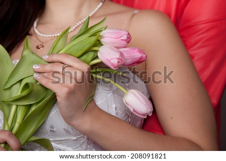 pink tulips in the hands of women, which hugs man closeup