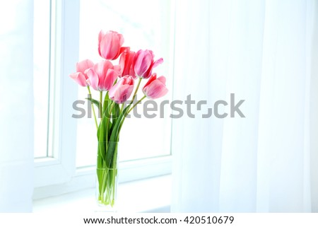 Pink tulips in vase on the windowsill - stock photo