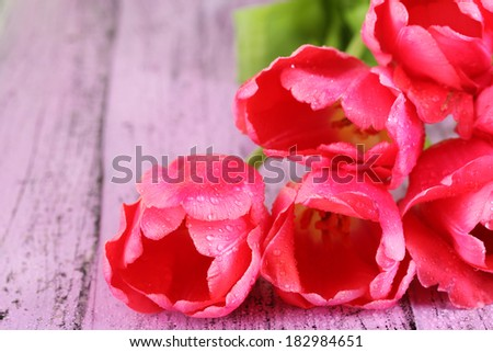 Pink tulips on wooden table - stock photo