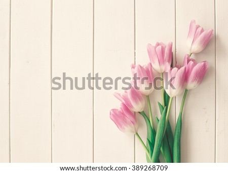 Pink tulips over a white wood table with copy space, in a flat lay composition  - stock photo