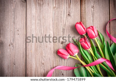 Pink tulips with a bow on wooden background with space for text - stock photo