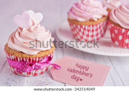 Pink Valentine cupcakes with the words 'Happy Valentine's day' on a tag. - stock photo