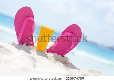 Pink vibrant beach flip flops with sunscreen protection face cream in white sand on sea background. Tropical summer vacation concept - stock photo