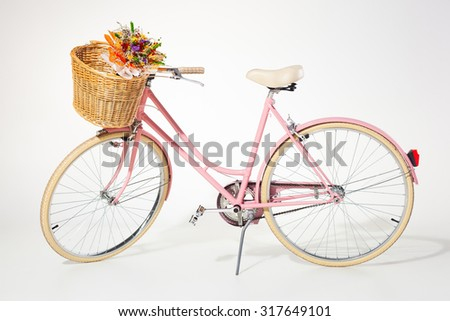 pink vintage bicycle with flower basket isolated on white background - stock photo