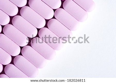 pink vitamin pills on white table