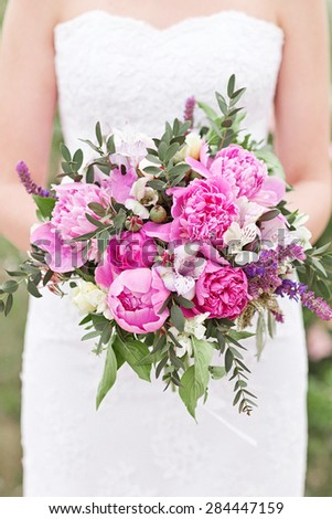 Pink wedding bouquet with peony, roses, orchids, and green leaves. Tenderness hand made accesessory for bride. - stock photo