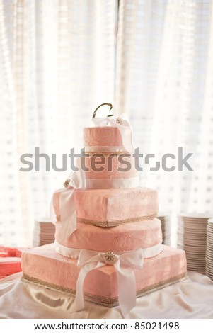 Pink wedding cake sitting in a reception hall. - stock photo