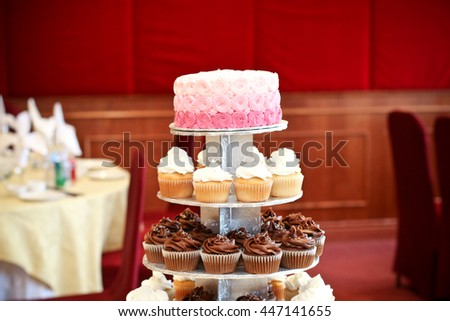 pink wedding cake with gourmet cupcakes