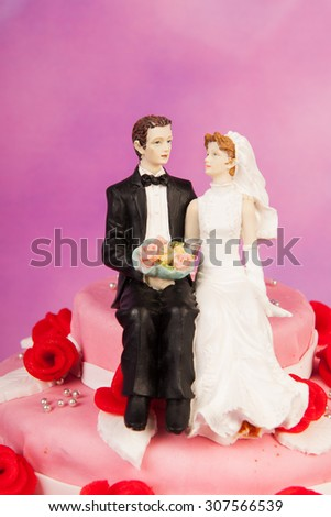 Pink wedding cake with red roses and vintage couple on top - stock photo