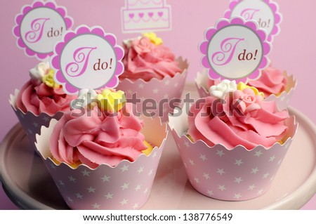 Pink wedding cupcakes with I Do topper signs on pink cake stand - close up. - stock photo