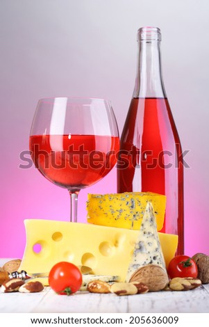 Pink wine and different kinds of cheese on colorful background - stock photo