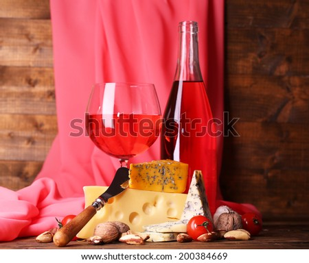Pink wine and different kinds of cheese on fabric background - stock photo