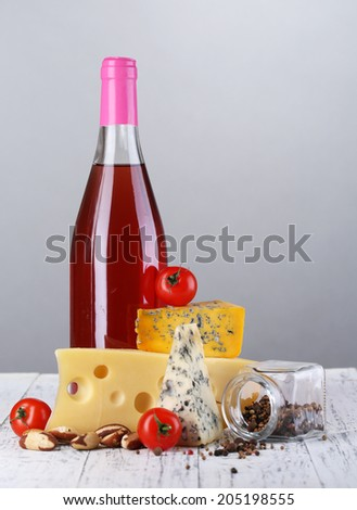 Pink wine and different kinds of cheese on grey background - stock photo
