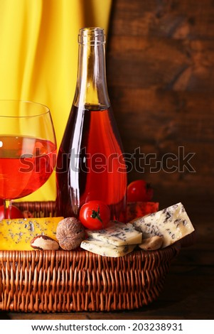 Pink wine and different kinds of cheese on wooden background - stock photo