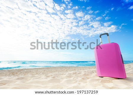 Pink women baggage bag on the sand on the beach on hot sunny day - stock photo