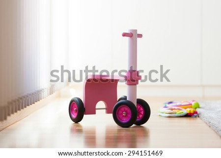 Pink wood bike toy in the middle of the living room