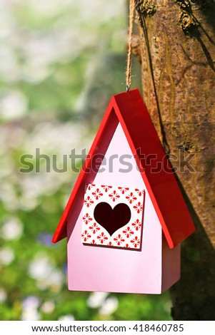 Pink wooden birdhouse with red roof and entrance heart hangs on  tree in spring forest on blurred background, close up - stock photo