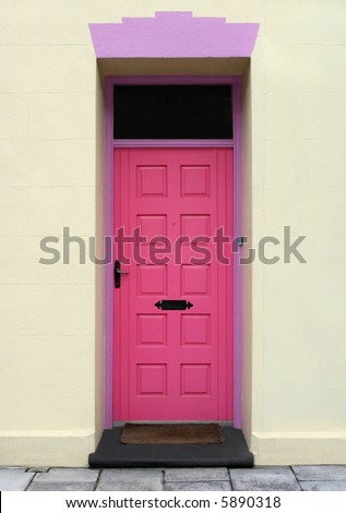 Pink wooden door with lilac colored surround and cream stonework. - stock photo