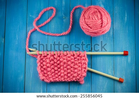 Pink woolen yarn ball and knitting needles on old vintage blue wooden background - stock photo